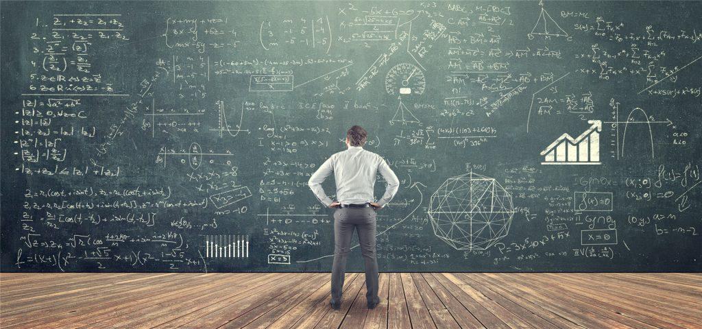 Student studying math on the blackboard full of formulas